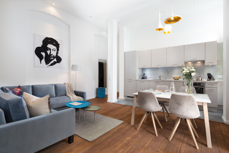 re-vamp: upholstery living; ku'damm altbau renovierung - berlin charlottenburg living room , a blue couch, 4 white dinning chairs around a square tables with flowers on top, one blue center table placed in front of the couch.