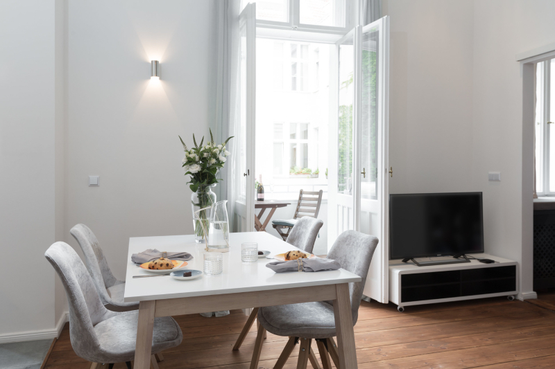re-vamp interior design: ku'damm altbau renovierung - berlin charlottenburg apartment, dinning space, 4 white chairs around a square table with some flowers on top and dinning plates.