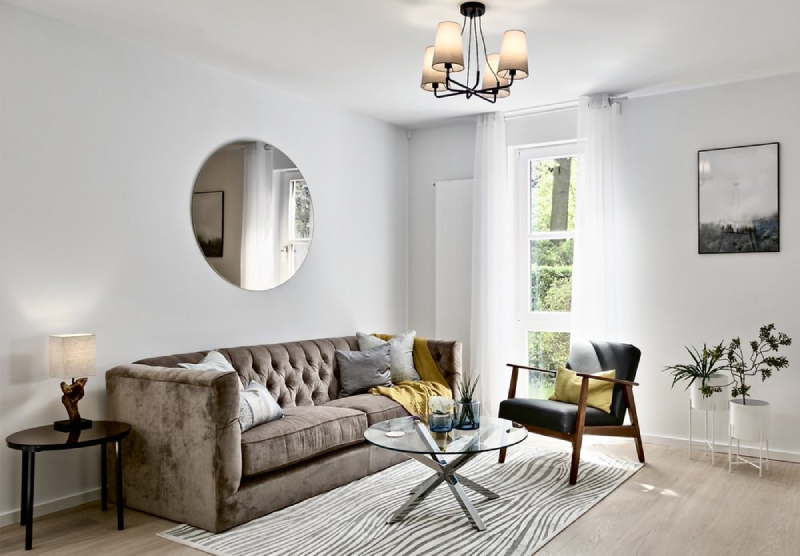 musterwohnung mit seeblick - berlin köpenick re-vamp. In this image we have 1 couch and 1 arm chair, a round mirror on the wall and a tiny round center table.