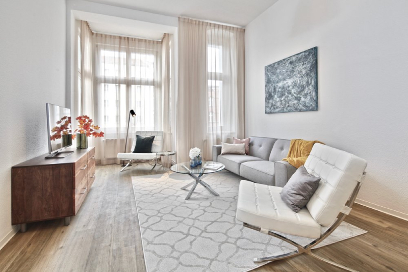 Re-vamp Interior Design: Upholstery Living im berlin friedrichshain. A living room with 2 white arm chairs, one gray couch, one white rug and a tint round center table on top.